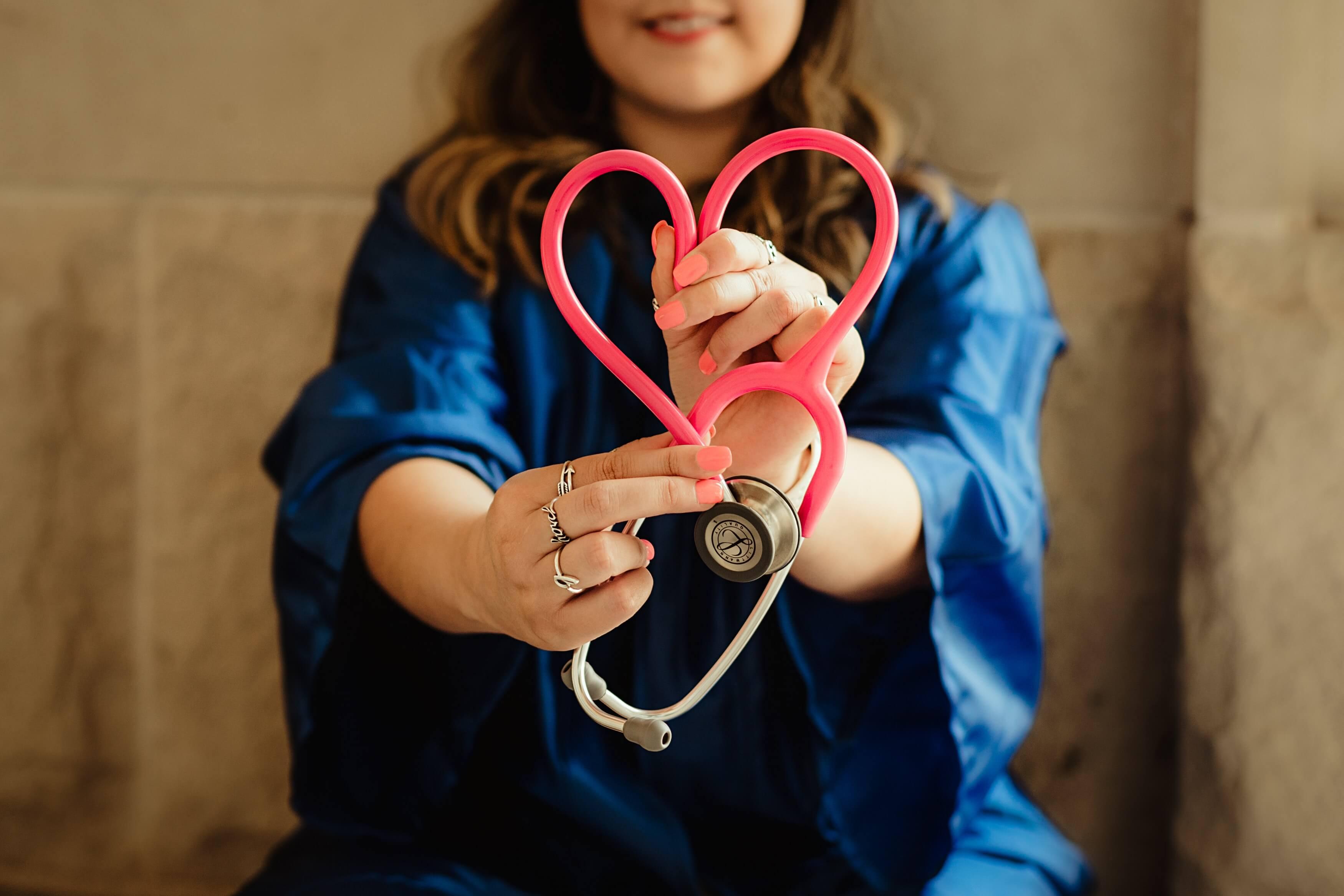 Medizinerin in Arbeitskleidung macht mit Stethoskop eine Herzform